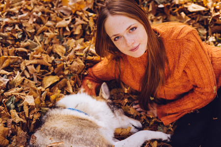 red-haired beautiful girl in an orange sweater playing with her dog in fallen autumn leaves