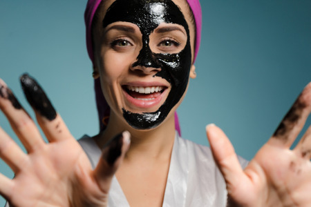 happy smiling girl looks after herself, puts a black cleansing mask on her face Stock Photo