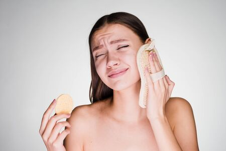 Dissatisfied young girl cleanses the skin on the face with a special sponge