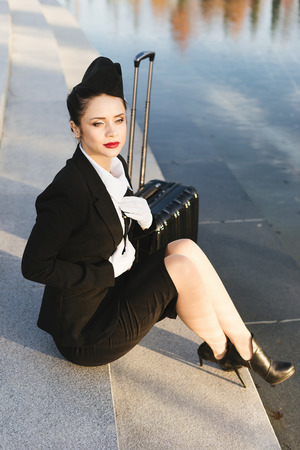 pensive beautiful stewardess woman in uniform, professional, sitting on steps in park, near water, with suitcase