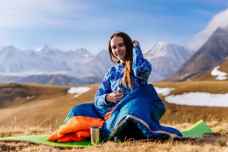 happy young girl in a blue jacket travels, enjoys the mountains and the sun Archivio Fotografico
