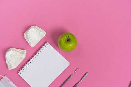 on a pink surface is a green apple, a white notebook, a plaster cast of teeth