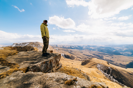 male traveler standing on the edge of the cliff against the background of the Caucasian mountains and blue sky