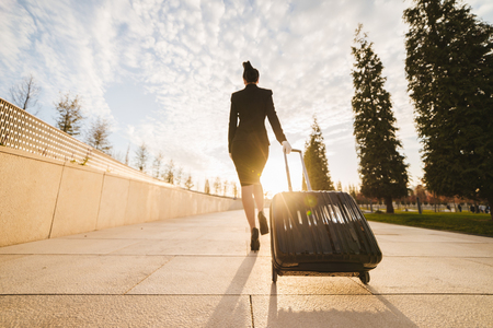 A female flight attendant in uniform with a suitcase goes on a flight, in the rays of the sun Banque d'images