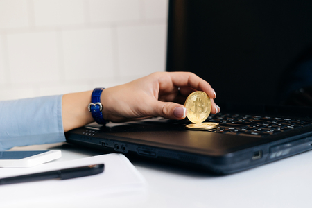 girl financier in a blue shirt works on a laptop and holds a gold bitcoin in her hand