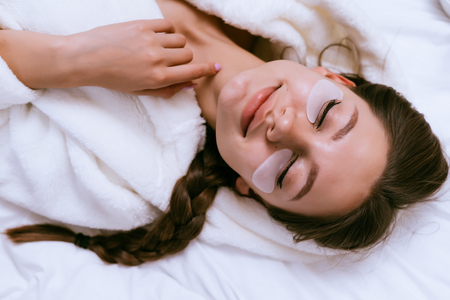 smiling happy girl lies in bed, under eyes white patches, eyes closed Stock Photo