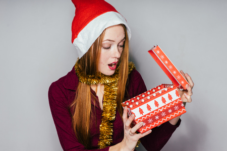 surprised red-haired girl in a red cap received a gift in a box for the new year 2018 Stock Photo