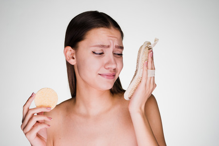 young disgruntled girl holding a small sponge and a large loofah