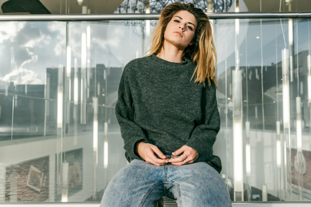 young girl in gray-green sweater sits leaning against glass barrier Stock Photo