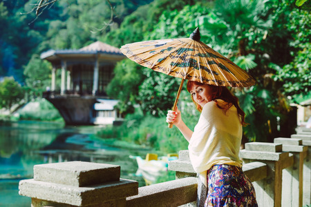 red-haired female traveler, walks in the park with a Chinese umbrella