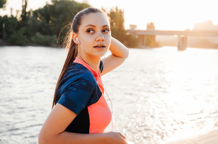 a girl in a sport uniform turns back while jogging