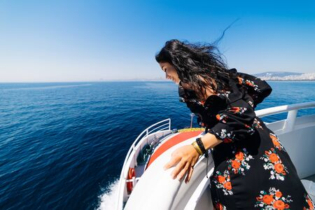 Happy smiling girl on yacht looks to the sea Stock Photo