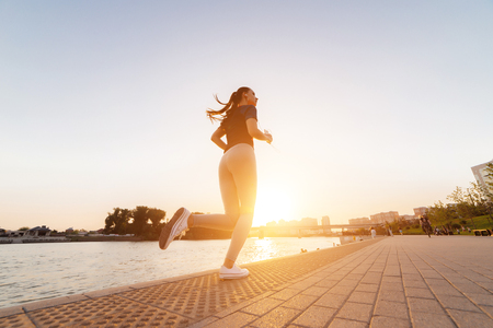 girl jogging near the river at sunset Stock Photo