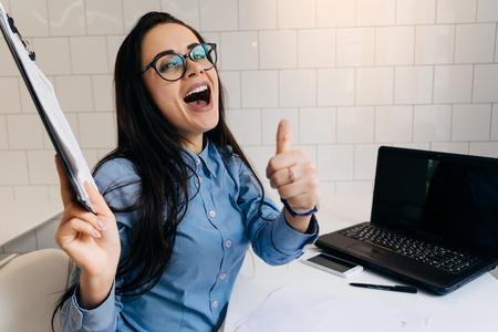 Girl secretary in glasses enjoys the work done Imagens