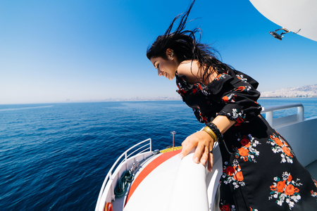 Happy beautiful tourist woman on private yacht