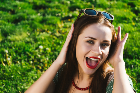 Smiling woman in sunglasses on a grass outsuide