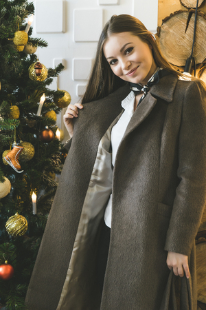 a young girl trying on a new coat on the background of a Christmas tree
