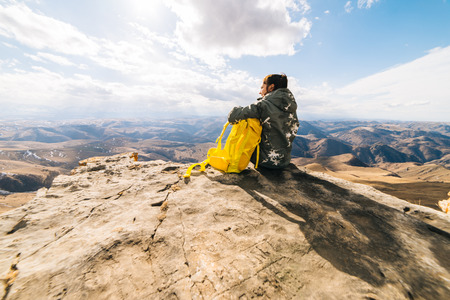 active girl sitting on the edge of the cliff with a yellow backpack, looking at the mountains