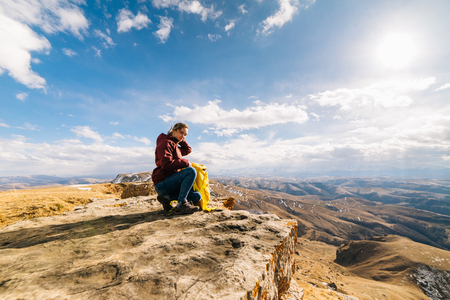 active young girl loves sports tourism, sits on the edge of the mountain in the rays of the sun