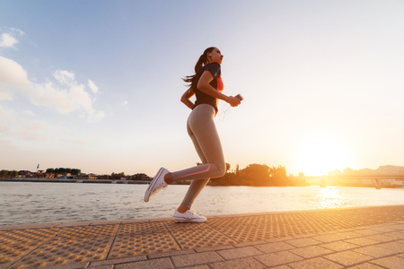 young girl in a sporty uniform performs an evening run