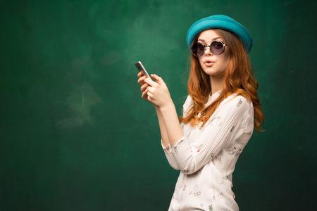 帽子と眼鏡をかけた若い女の子が電話の誰かと一緒にいる