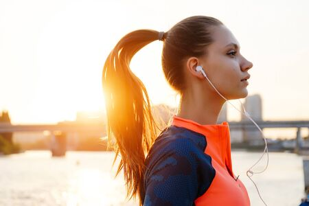 Portrait of young female runner jogging near river front and bridge Stock Photo