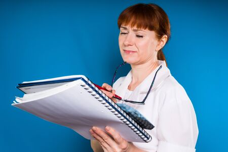 woman on a blue background in a medical dressing gown examines documents