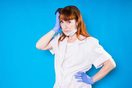 adult female doctor with a frown on his arm against a blue background Banque d'images