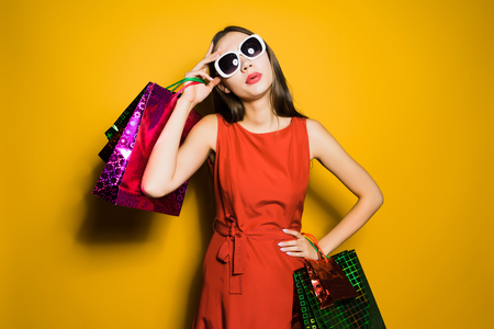 a young stylish girl in a red dress and sunglasses bought a lot of gifts for the new year 스톡 콘텐츠