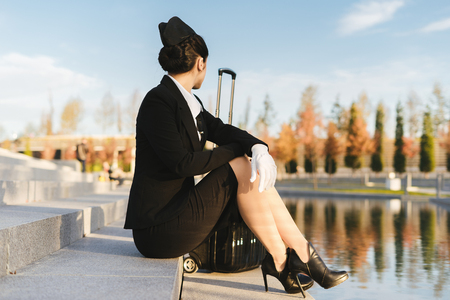 stewardess with a black suitcase sitting on the steps