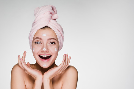 young girl with a towel on her head laughing put on face mask