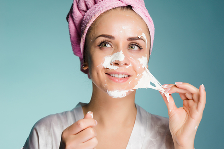 girl after shower with a towel on her head removes the cleansing mask from the face