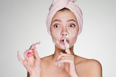 girl with a towel on her head makes an epilation on her face with a razor