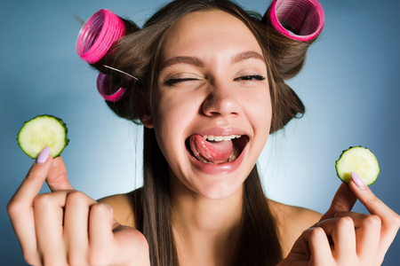 a funny young girl shows her tongue, holds pieces of cucumber to moisten the skin on her face, on her head curlers