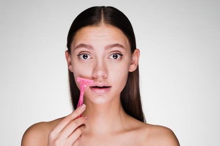 young attractive girl shaves a mustache with a pink razor