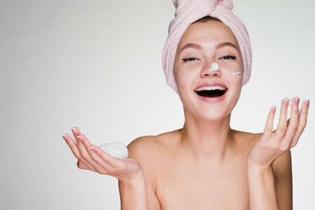 Laughing attractive girl with towel on head applying moisturizer on face Stock Photo