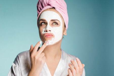 a young thoughtful girl with a pink towel put on her face a white moisturizing mask