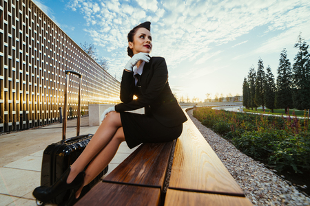 girl stewardess with a suitcase on a cloudy sky background