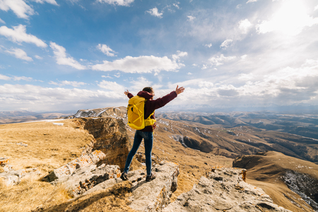 young girl with a yellow backpack in the background of high mountains 写真素材