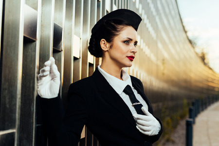 young girl stewardess in white gloves against the building background Stock Photo