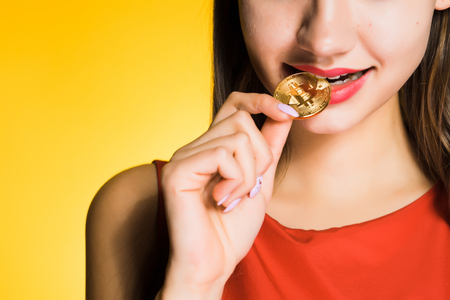 girl in red dress tries golden bitcoin to taste, on yellow background Фото со стока