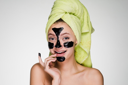 attractive young girl with a green towel on her head, with a black cleansing mask on her face smiling