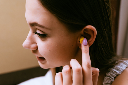 a cute young girl wants to sleep, inserts in her ears yellow earplugs against street noise
