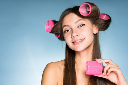 smiling beautiful girl doing a stylish hairstyle with a big pink hair curler