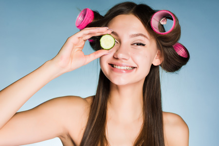 smiling girl with curlers on her head holding a piece of cucumber for moisturizing the skin on her face Stock Photo