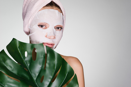 a girl wants to be beautiful, a moisturizing tissue mask on her face, a towel on her head, a spa procedure