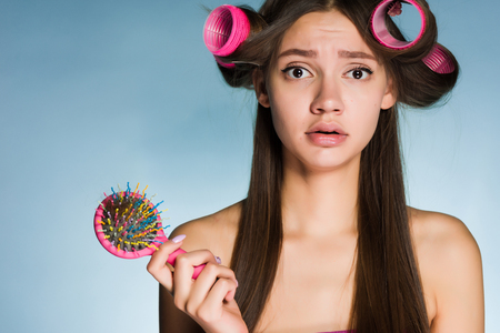 sad young girl can not make a beautiful hairstyle, on the hair curler head, keeps comb Stock Photo