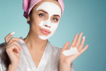 Ein junges Mädchen mit einem rosa Handtuch auf ihrem Kopf legt eine weiße Maske auf ihr Gesicht für die Kopfhaut Standard-Bild
