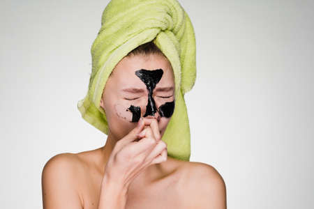 A young girl with a green towel on her head takes off a black mask from her face, it hurts Stock Photo