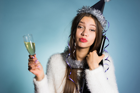 drunk funny young girl celebrating the new year, holding champagne in her hands